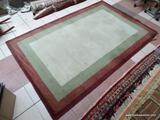 ESTATE OWNED HAND TUFTED RUG IN IVORY, GREEN, AND MAROON. MEASURES APPROXIMATELY 5 FT 1 IN X 7 FT 9
