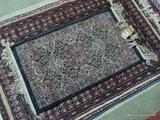 MACHINE MADE ORIENTAL STYLE RUG IN BLUE, IVORY, AND RED. MEASURES APPROXIMATELY 1 FT 7 IN X 3 FT.