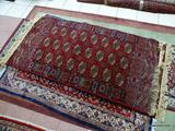HANDMADE MACHINE TURKISH RUG IN MAROON, IVORY, AND BLUE. MEASURES APPROXIMATELY 3 FT X 6 FT. ITEM IS