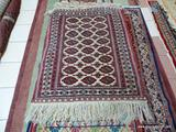 HANDMADE ORIENTAL BOKHARA IN IVORY, RED, AND BLUE. MEASURES APPROXIMATELY 3 FT 8 IN X 5 FT. ITEM IS