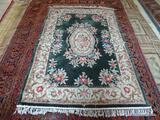 HANDMADE SCULPTED CHINESE RUG IN GREEN, IVORY, AND MAUVE. MEASURES APPROXIMATELY 4 FT 6 IN X 5 FT 7