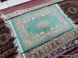 HANDMADE ORIENTAL RUG IN GREEN, IVORY, AND PINK. MEASURES 1 FT 11 IN X 3 FT 3 IN. DOES SHOW SOME