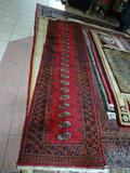 HANDMADE BOKHARA RUNNER IN RED, BLACK, AND ORANGE. MEASURES APPROXIMATELY 2 FT 7 IN X 10 FT 1 IN.