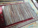 HAND WOVEN LEATHER BRAIDED RUG IN MULTI COLORS. MEASURES APPROXIMATELY 3 FT 9 IN X 6 FT 3 IN. ITEM