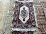 HANDMADE INDIAN RUG IN IVORY, BLUE, AND RED. MEASURES APPROXIMATELY 2 FT X 3 FT. ITEM IS SOLD AS IS