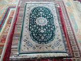 HAND KNOTTED FINELY WOVEN PERSIAN IN GREEN, IVORY, AND BLUE. MEASURES APPROXIMATELY 3 FT X 5 FT 2