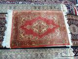 HANDMADE ORIENTAL RUG IN RED, IVORY, AND GREEN. MEASURES APPROXIMATELY 2 FT 3 IN X 3 FT. ITEM IS