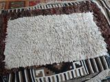 BRAIDED COTTON RUG IN IVORY. MEASURES APPROXIMATELY 2 FT 2 IN X 3 FT 9 IN. ITEM IS SOLD AS IS WHERE