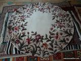 ROUND CHINESE SCULPTED RUG IN IVORY, BROWN, AND MAUVE. MEASURES APPROXIMATELY 5 FT 6 IN DIA. ITEM IS