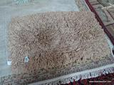 SHAGGY BRAIDED RUG IN BROWN. MEASURES APPROXIMATELY 2 FT 6 X 4 FT 2 IN. ITEM IS SOLD AS IS WHERE IS