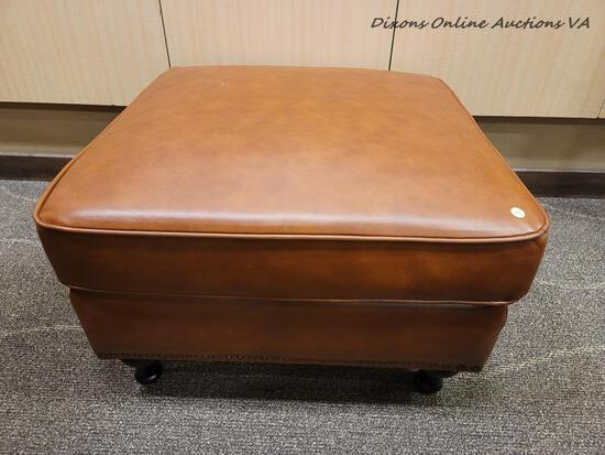 (R1) MODERN LEATHER UPHOLSTERED OTTOMAN IN BROWN WITH ESPRESSO FINISH LEGS. MEASURES 29 IN X 29 IN X