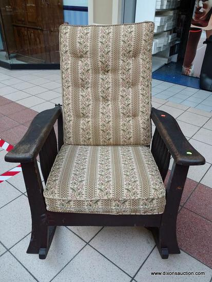 (R1) ANTIQUE ADJUSTABLE ANGLE BACK ROCKING CHAIR WITH TAN AND GREEN CUSHIONS. MEASURES 31 IN X 34 IN