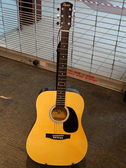 (SC) SQUIER BY FENDER ACOUSTIC GUITAR. MODEL 093-0300-021. SERIAL #0060100523. INCLUDES A STRAP. AND