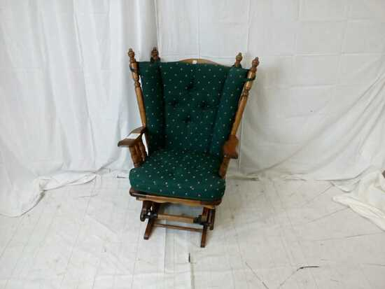 Dark oak glider rocker with green seat and back.