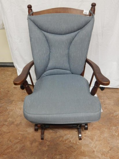 Dark wood and fabric glider rocker. Blue fabric is stained