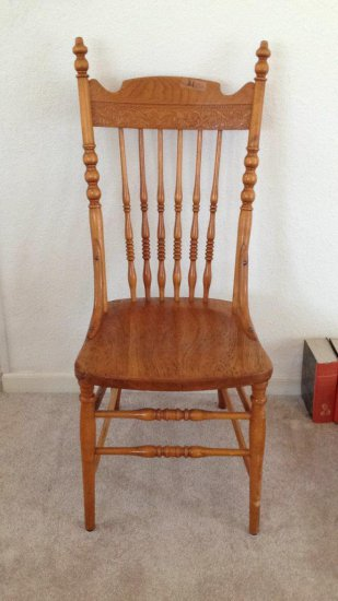 Vintage oak dining chair with spindle back carvings.
