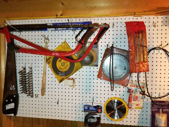 TOOLS ON PEGBOARD INCLUDING HAND SAWS, BLADES, AND MORE. PEGBOARD DOES NOT