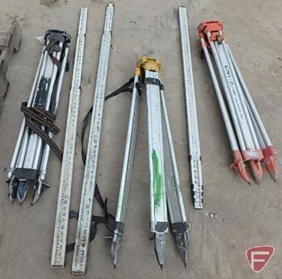 (3) Surveyor tripod bases and (3) and measuring sticks
