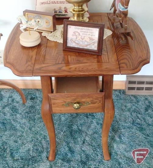 Drop leaf end table with drawer, table lamp, and decorative items.