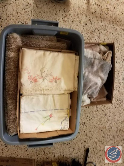 Tote and box containing kitchen dish cloths, rugs, and linens.