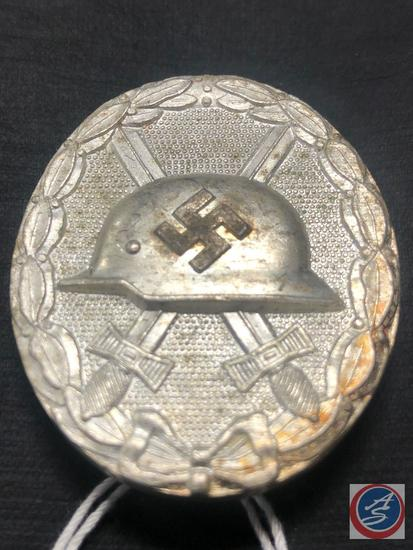 German World War II Silver Wound Badge. The front shows a German helmet in the center with a pair of