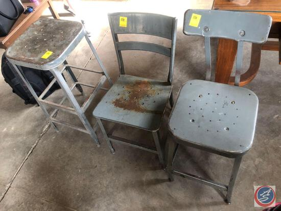 (3) chairs / stools. (1) is a gray, Lyon brand stool made of metal; (1) is a gray, Lyon brand stool