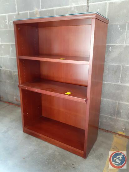 wood bookcase with four shelves (three are adjustable). The back of the bookcase appears to be