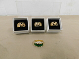 (3) MENS GOLD TONE EAGLE RINGS & (1) WOMANS GOLD TONE W/ GREEN STONES RING