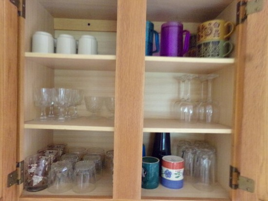 CONTENTS OF KITCHEN CABINET INCLUDING STEMWARE COFFEE MUGS SOUP BOWLS AND M