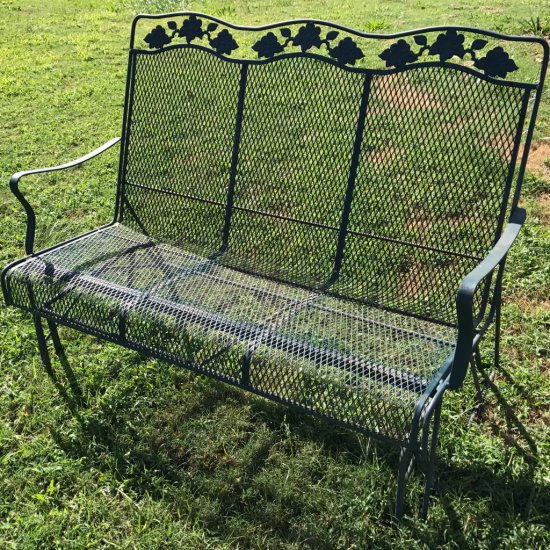 Green Wrought Iron Outdoor Glider with Ivy Design Top
