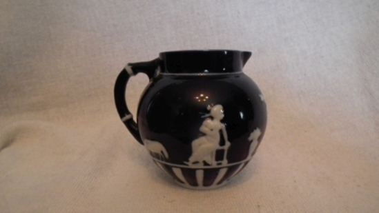 "Dark blue & white creamer, woman & animal design, a few stray blue paint dots on bottom, 3/5""H x 4""W"