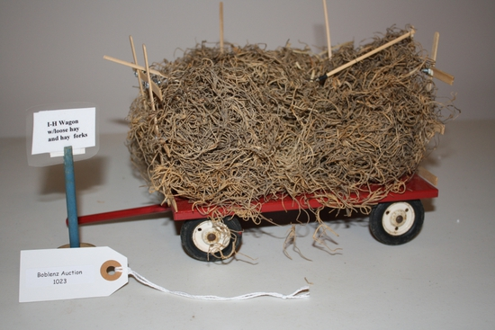 International Harvester wagon w loose hay and hay forks
