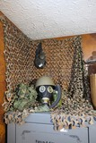 Camo netting, two gas masks, military helmet, web gear lot