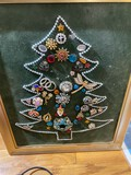 Stack of art including costume jewelry Christmas tree, paintings