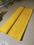 Large yellow shag rug or carpet