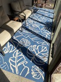 2 larger sized blue outdoor carpets