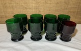 7 Heavy Green Glass Glasses and 1 Red .
