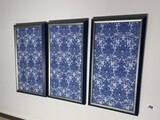 Three framed blue and white fabric pieces