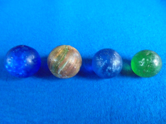 (4) OLD FLAKE TYPE MARBLES-PLAYED WITH IN DIFFERENT COLORS