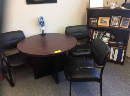 Round table, three chairs and a bookshelf. Contents not included