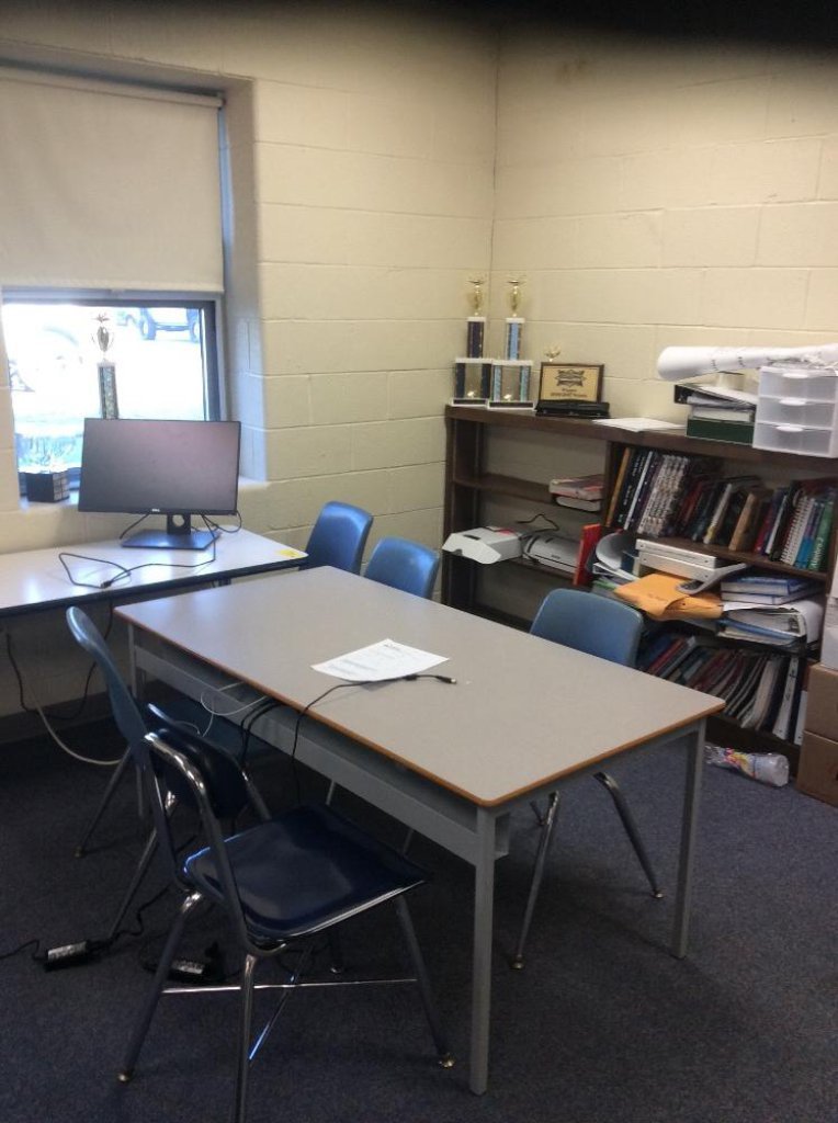 Two student tables and six chairs and a wooden bookcase. Contents not included