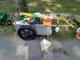 Metal garden cart with gardening sprays, pruner, spreader