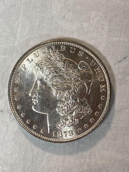 1878 Morgan dollar, (8) tail feathers, AU grade.