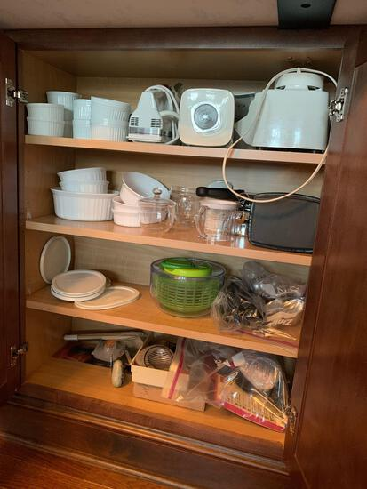 Kitchenware contents from kitchen island lower cabinetry