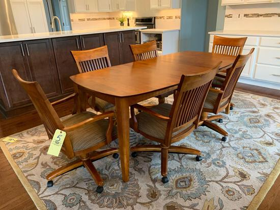 Solid wood dining table with 6 chairs on casters and 1 extra leaf and pads