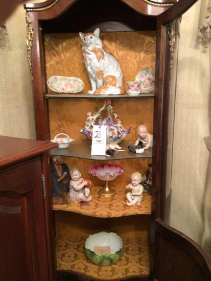 Assorted figurines and glassware in China cabinet