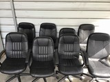 Eight black leather office chairs