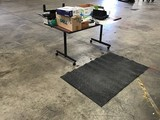 Table with office supplies , floor mat