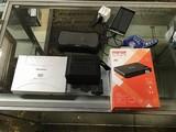 Black speaker, magnavox media player, grey smartphone, Black speaker, portable charger, micro projec