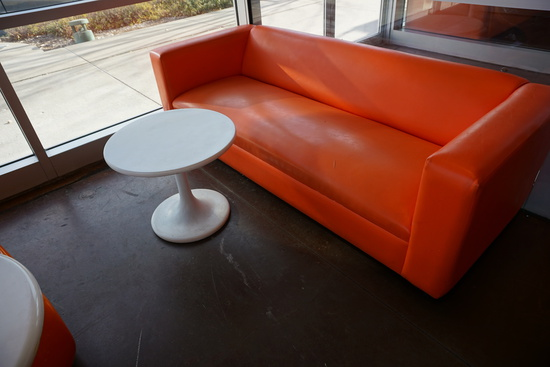6' Orange Low Couch & Round Plastic White Table.